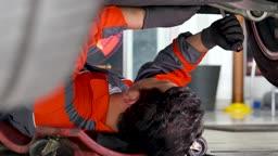 자동차 정비소 누워서 하부 너트 체결하는 정비사 모습