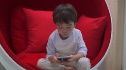 핸드폰으로 미디어 시청하는 남자아이 모습