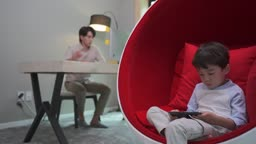 재택근무하는 남자와 핸드폰으로 미디어 시청하는 남자아이 모습