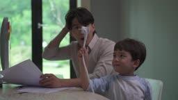 컴퓨터 전원 코드를 뽑아드는 남자아이와 놀라는 남자 모습