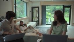 거실에 모여앉아 전자기기 사용하는 가족 모습