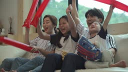 거실에 모여앉아 야구 시청하며 응원하는 가족 모습