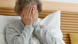 실버요양 침대에서 얼굴을 가리고 우울해하는 할머니 모습