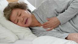실버요양 침대에 누워 가슴 답답해하는 할머니 모습