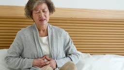 실버요양 침대에 앉아 복통을 호소하는 할머니 모습