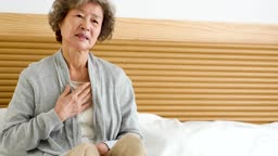 실버요양 침대에 앉아 가슴 통증을 호소하는 할머니 모습