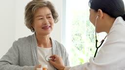 병원 청진기로 진료를 보는 할머니와 의사 모습