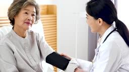 재택진료 침대에 앉아 혈압재는 할머니와 의사 모습