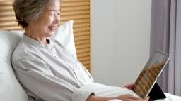 원격진료 침대에 앉아 태블릿피씨로 원격진료 보는 할머니와 의사 모습