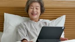 원격진료 침대에 앉아 태블릿피씨로 원격진료 보는 할머니 모습