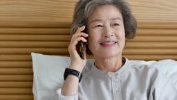 원격진료 침대에 앉아 스마트폰으로 통화하며 진료보는 할머니 모습