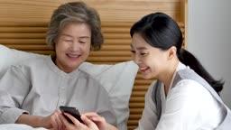 간병 침대에서 할머니 스마트폰 사용법 알려주는 요양 보호사 모습
