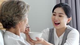 간병 침대에서 할머니 식사를 도와주는 요양 보호사 모습