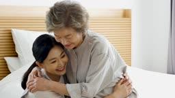 간병 침대에서 할머니 손으로 부축해주는 요양 보호사 모습