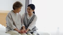 간병 침대에 앉아 담소 나누는 할머니와 요양 보호사 모습