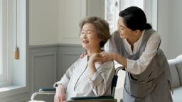 간병 휠체어 탄 할머니와 요양 보호사 모습