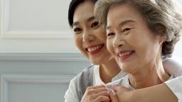 간병 카메라 응시하며 미소짓는 할머니와 요양 보호사 모습