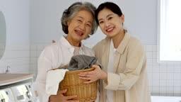 공동생활 세탁실에서 세탁 바구니를 들고 있는 할머니와 젊은여자 모습