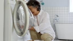 공동생활 세탁실에서 즐겁게 세탁물을 세탁기에 넣고 있는 할머니 모습