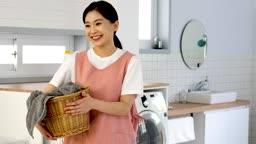 공동생활 세탁실에서 세탁 바구니를 들고 미소짓고 있는 젊은여자 모습