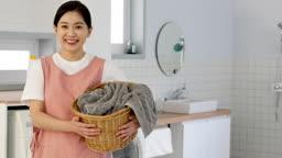 공동생활 세탁실에서 세탁 바구니를 들고 미소지으며 카메라 응시하는 젊은여자 모습