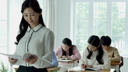 초등학교 교실에서 교과서를 보고 있는 선생님과 공부하는 학생들 모습