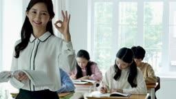 초등학교 교실에서 카메라 응시하며 포즈 취하는 선생님과 공부하는 학생들 모습