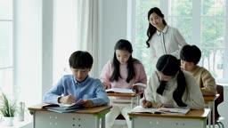 초등학교 교실에서 공부하는 학생들과 수업을 감독하는 선생님 모습