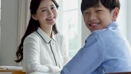 초등학교 교실에서 선생님과 학생이 카메라 응시하며 미소짓는 모습