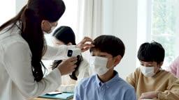 초등학교 교실에서 체온계로 온도 측정하는 선생님과 학생 모습