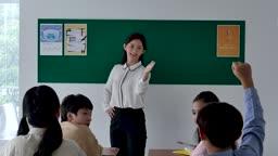 초등학교 교실에서 손을 든 학생과 수업을 진행하는 선생님 모습