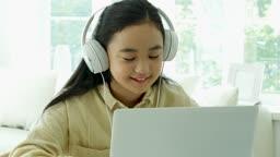 온라인 교육 헤드폰 착용하고 노트북으로 미소지으며 수업 듣는 학생 모습