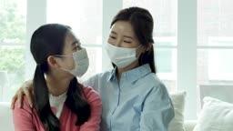 마스크 착용하고 소파에 앉아 카메라 응시하며 미소짓는 엄마와 딸 모습