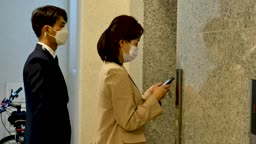 일상 생활 속 마스크 마스크 착용하고 아파트 엘리베이터 앞에서 기다리는 비즈니스맨과 비즈니스우먼 모습