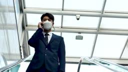일상 생활 속 마스크 마스크 착용하고 에스컬레이터 타면서 통화하는 비즈니스맨 모습