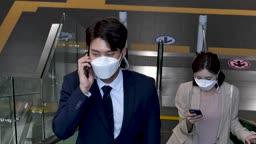일상 생활 속 마스크 마스크 착용하고 에스컬레이터 타면서 스마트폰하는 비즈니스맨과 비즈니스우먼 모습