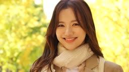 가을감성 공원 카메라 응시하며 미소짓는 젊은여자 모습