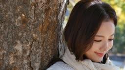 가을감성 공원 나무에 기대어 미소짓는 젊은여자 모습