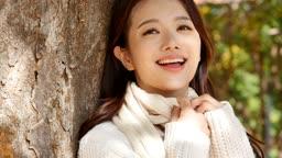 가을감성 공원 나무에 기대어 미소 지으며 가을을 만끽하는 젊은여자 모습