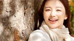 가을감성 공원 나무에 기대어 카메라 응시하며 미소짓는 젊은여자 모습