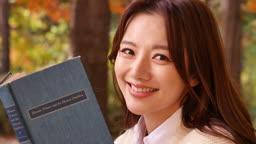 가을감성 공원 벤치에 앉아 책을 들고 카메라 응시하며 미소짓는 젊은여자 모습