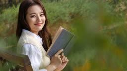 가을감성 공원 벤치에 앉아 카메라 응시하며 미소짓는 젊은여자 모습