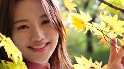 가을감성 공원 단풍나무 아래 카메라 응시하며 미소짓는 젊은여자 모습