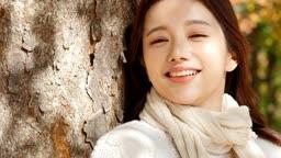 가을감성 공원 나무 아래 카메라 응시하며 미소짓는 젊은여자 모습