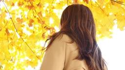 가을감성 공원 나무 아래 뒤돌아 카메라 응시하며 미소짓는 젊은여자 모습