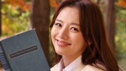가을감성 공원 책을 들고 카메라 응시하며 미소짓는 젊은여자 모습