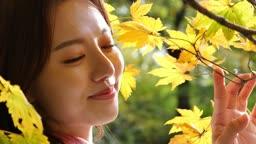 가을감성 궁원 단풍나무 아래 카메라 응시하며 미소짓는 젊은여자 모습