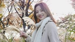 가을감성 공원 억새밭에서 카메라 응시하며 미소짓는 젊은여자 모습