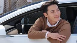 전기자동차 창문에서 고개를 내밀어 미소짓는 젊은남자 모습