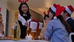 홈파티 크리스마스 거실 테이블에 앉아 선물을 전달하는 친구들 모습